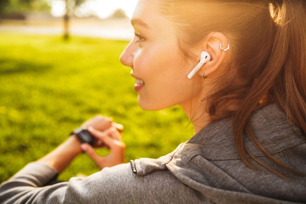 Girl wearing ear buds while running