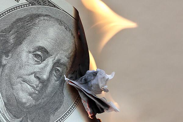 Dollar banknote wasted because of lacking good money-saving habits