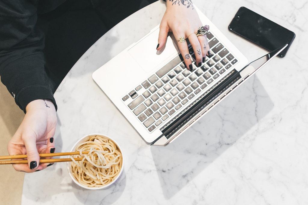 Woman does multitasking: food, laptop, phone.
