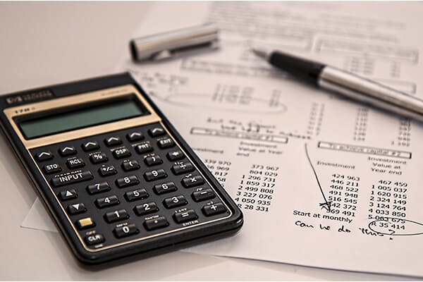 Calculator and sheets illustrating the action of creating a budget, one of the top money-saving tips.