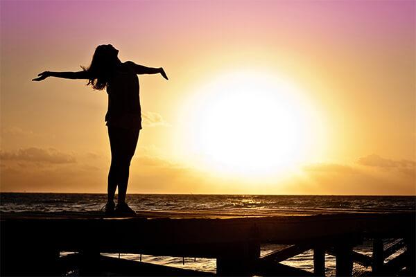 Debt-free woman enjoying sunset after applying money-saving tips.