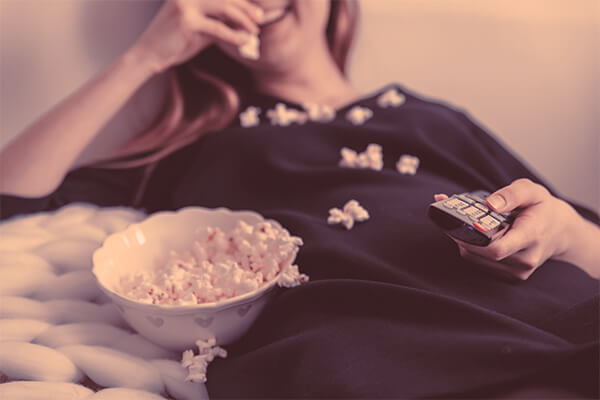 Woman-watching-Netflix in bed and eating popcorn