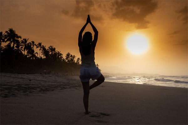 Woman on a beach using yoga poses to improve her mental health