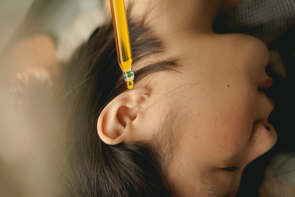 Young woman applying oil into her left ear as part of her yogi morning routine.