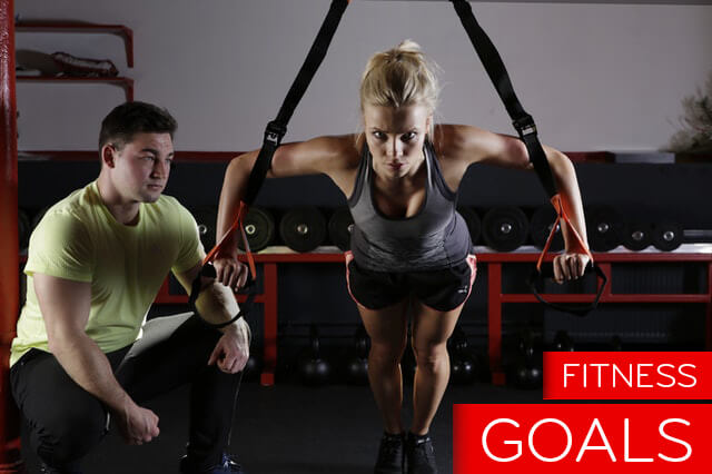 Man and woman achieving their fitness goals in the gym
