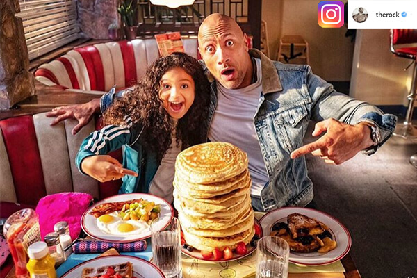 The Rock and little girl eating pancakes at a restaurant