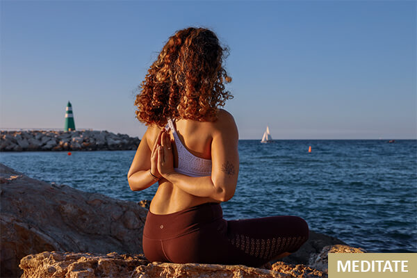 Female yogi meditates during her morning routine in front of the ocean.