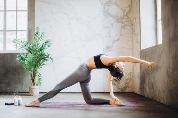 Yoga master showing beginners to chase their flexibility fitness goals